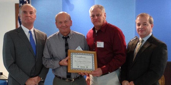 Jack Fehn and Gunther Karlowitsch accepted the certificate on behalf of the college.