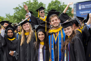 A group of smiling TCNJ graduates at the 2019 commencement ceremony.